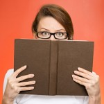 woman hiding behind book